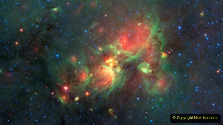 """Volunteers using the web-based Milky Way Project brought star-forming features nicknamed """"yellowballs"""" to the attention of researchers, who later showed that they are a phase of massive star formation. The yellow balls -- which are several hundred to thousands times the size of our solar system -- are pictured here in the center of this image taken by NASA's Spitzer Space Telescope. Infrared light has been assigned different colors; yellow occurs where green and red overlap. The yellow balls represent an intermediary stage of massive star formation that takes place before massive stars carve out cavities in the surrounding gas and dust (seen as green-rimmed bubbles with red interiors in this image).   Infrared light of 3.6 microns is blue; 8-micron light is green; and 24-micron light is red."""