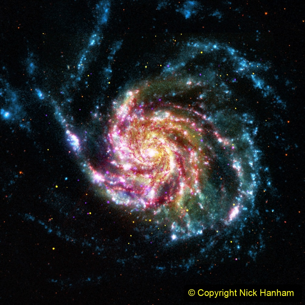 This image of the Pinwheel Galaxy, or M101, combines data in the infrared, visible, ultraviolet and x-rays from four of NASA's space telescopes. This multi-spectral view shows that both young and old stars are evenly distributed along M101's tightly-wound spiral arms. Such composite images allow astronomers to see how features in one part of the spectrum match up with those seen in other parts. It is like seeing with a regular camera, an ultraviolet camera, night-vision goggles and X-Ray vision, all at once! The Pinwheel Galaxy is in the constellation of Ursa Major (also known as the Big Dipper). It is about 70% larger than our own Milky Way Galaxy, with a diameter of about 170,000 light years, and sits at a distance of 21 million light years from Earth. This means that the light we're seeing in this image left the Pinwheel Galaxy about 21 million years ago - many millions of years before humans ever walked the Earth.  The red colors in the image show infrared light, as seen by the Spitzer Space Telescope. These areas show the heat emitted by dusty lanes in the galaxy, where stars are forming. The yellow component is visible light, observed by the Hubble Space Telescope. Most of this light comes from stars, and they trace the same spiral structure as the dust lanes seen in the infrared. The blue areas are ultraviolet light, given out by hot, young stars that formed about 1 million years ago. The Galaxy Evolution Explorer (GALEX) captured this component of the image. Finally, the hottest areas are shown in purple, where the Chandra X-ray observatory observed the X-ray emission from exploded stars, million-degree gas, and material colliding around black holes.
