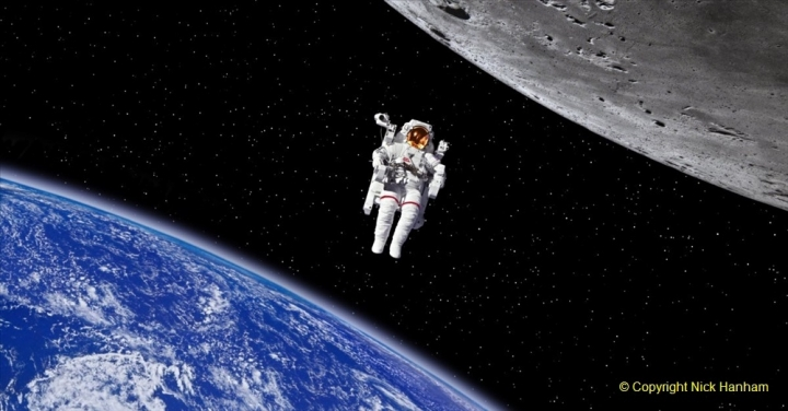 Astronaut on spacewalk in front of planet Earth and Moon