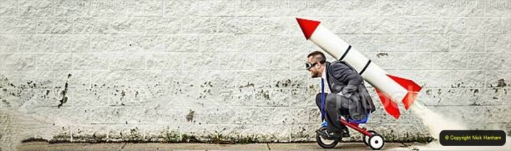 Businessman riding a tricycle and getting help from the rocket strapped to his back :-)